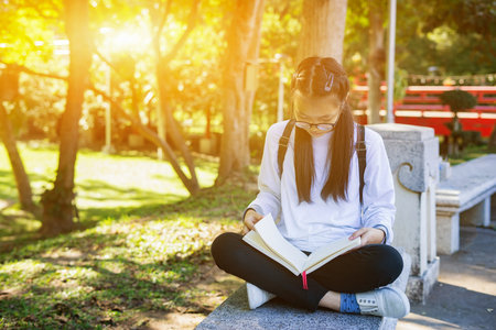 Pretty relaxed young girl reading book at park in summer sunset light,vintage color.