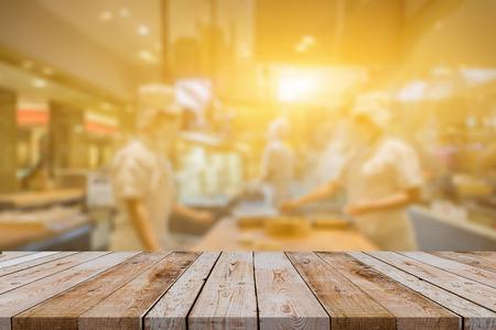 Vaciar la mesa de madera con desenfoque abierta cocina restaurante de fondo, cocineros de los chefs en la cocina el cliente puede ver que son cocinero en el mostrador de alimentos, Mock Up plantilla para el montaje de su producto, el color de la vendimia