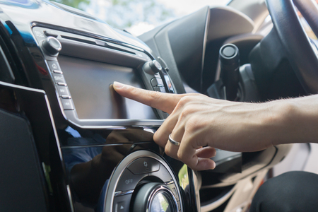 Transportation,technology and vehicle concept - man using car system control pushing panel button touch screen interface modern design,GPS and DVD ,Vintage color Banque d'images