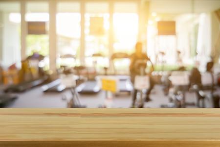 空ブラウン木製テーブル フィットネス ジム、スポーツ、インテリア機器と新しい近代的なクラブの男女の若者グループの背景をぼかした写真のトッ