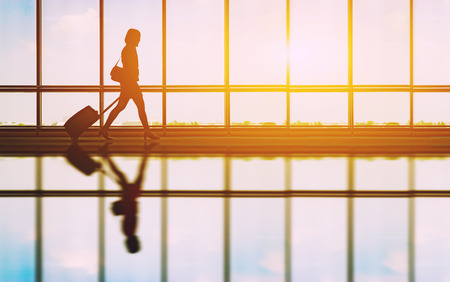 travel concept, people in the airports ,Silhouette of young girl with luggage walking at airport, women showing something through the window,selective focus,vintage tone color Imagens