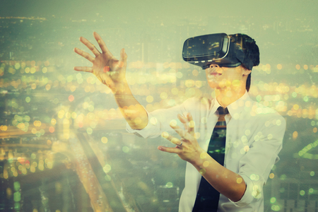 double exposure man wearing virtual reality  in modern coworking studio. Smartphone using with VR Box 3D Virtual Reality  Glasses headset,vintage color Lizenzfreie Bilder