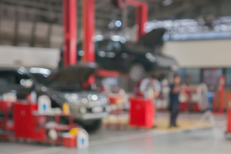 Blurred background of technician repairing the car in garage,mechanics fixing in a workshop suspension detail of lifted automobile at service station,vintage color. Reklamní fotografie