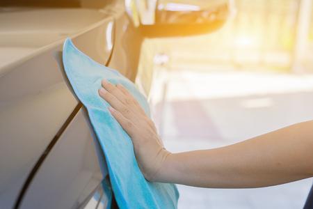 Mano con seduta in pelle di pulizia panno in microfibra, dettagli auto e valeting concetto, lavaggio interno la cura dell'auto, messa a fuoco selettiva, colore d'epoca Archivio Fotografico - 73815918