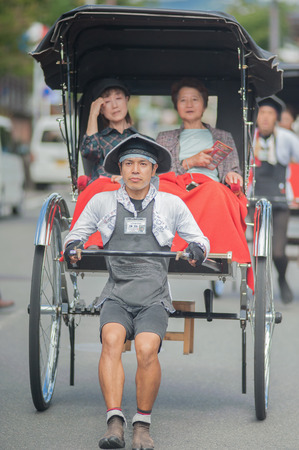 KYOTO, JAPAN - NOVEMBER 10: Rickshaw in Kyoto, Japan on November 10, 2014. Unidentified man with a rickshaw and tourists near Tenryuji Temple