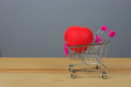 red heart shape on mini shopping carts filled with Valentines day hearts on wooden table with room for your text or images, represents Love and Romance,