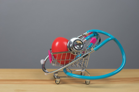 Stethoscope and  red heart shape on mini shopping carts filled with Valentines day hearts on wooden table with room for your text or images, represents Love and Romance,