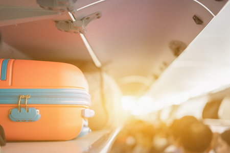 Handbagage op de bovenste plank boven op het vliegtuig, passagier zet zak cabine compartiment vliegtuig, vintage kleur, kopie ruimte Stockfoto