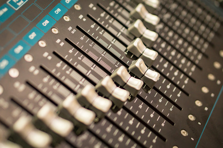 Side closeup on a sliders of a mixing console. It is used for audio signals modifications to achieve the desired output. Applied in recording studios, broadcasting, television and film post-production Stock Photo