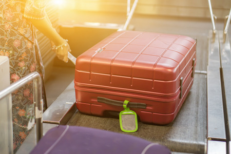 luggage at Point of checking the luggages scanner. Baggage check-in ,X-ray machine band on the on conveyor belt at the airport counter.selective focus,vintage color