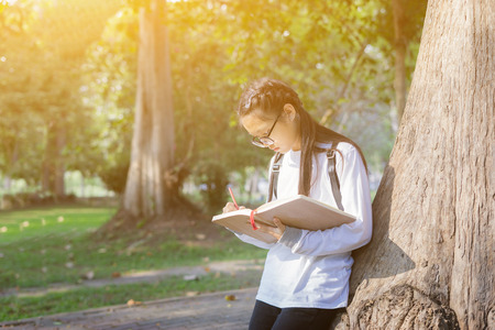 young girl student writes information from portable net-book while prepare for lectures in University campus and reading a book,vintage color,selective focus,education concept