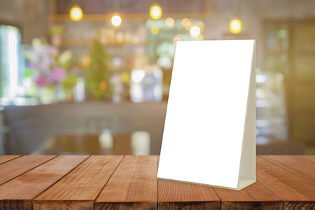 reserved: Empty brown wooden table and Coffee shop interior with Mock up Menu frame in Bar restaurant ,Stand for booklets with white sheets of paper acrylic tent card on cafeteria blurred background