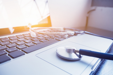 Stethoscope and laptop keyboard on desktop in hospital,relax time doctor,medical concept,selective focus,vintage color.morning light