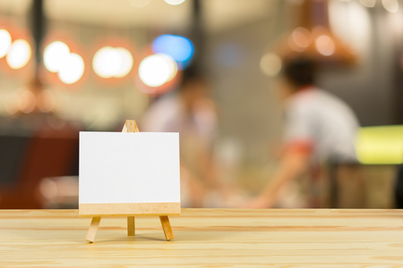 Easel with blank canvas on wooden table,billboard on wood desk top with supplied bokeh background,Template mock up for montage of display your product.vintage color