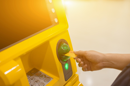 Hand inserting ATM card into bank machine to withdraw ,People stand in a queue to receiving money.vintage color