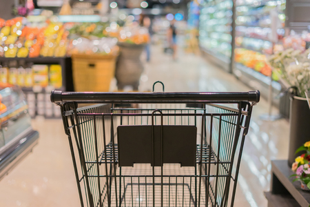 Abstract blurred photo of trolley in department store bokeh background,empty shopping cart in supermarket ,vintage color 免版税图像