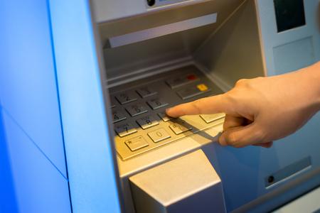 Vrouwelijke hand die wachtwoord indient voor het onttrekken van geld van binnenbank ATM, Thaise Baht-biljetten bij Automatic Teller Machine, selectieve focus, vintage kleur