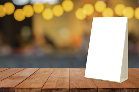 Empty brown wooden table and Coffee shop interior with Mock up Menu frame in Bar restaurant ,Stand for booklets with white sheets of paper acrylic tent card on cafeteria blurred background Imagens - 77164362