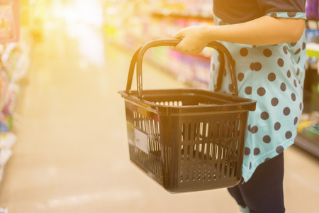 Female Hand  holds a shopping basket   in a Supermarket Walking Trough the Aisle, in department store bokeh background,vintage color,copy space Stock Photo