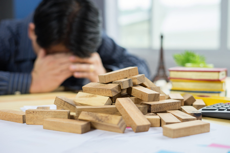 Failure Business,Problem Solving,businessman cant stop effect of dominoes continuous toppled with hand at desk,retro style image executive and risk control concept,selective focus,vintage color