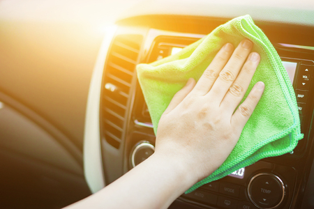 valeting: Hand with microfiber cloth cleaning leather seat,auto detailing and valeting concept,washing car care interior,selective focus,vintage color Stock Photo