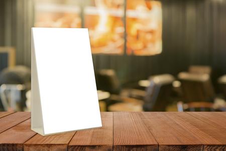 Vaciar la mesa de madera marrón y cafetería interior con Mock up Marco de menú en el restaurante Bar, Stand para folletos con hojas blancas de papel tarjeta de tienda de acrílico en la cafetería fondo borroso Foto de archivo - 77164554