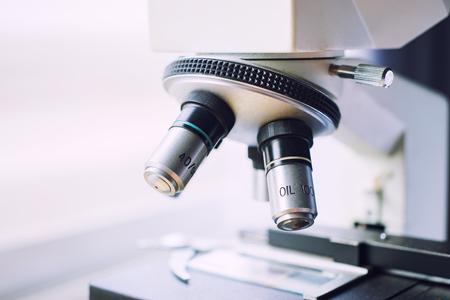 医療研究所化学顕微鏡を使用して科学者の手は、サンプル、サンプルを調べると液体・医療機器をテストします。顕微鏡・医療研究 background.vintage 色