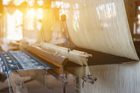 weave silk cotton on the manual wood loom,vintage color Stock Photo