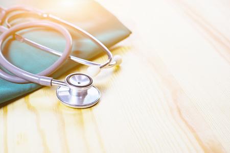 聴診器・医療機器医師やコートの浅い自由度が均等にマッチした木製のテーブルと背景、時間、選択と集中、ヴィンテージ色の机の上に休んで、リ