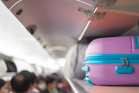 Carry-on luggage on the top shelf  over head on airplane, passenger put bag cabin compartment air craft ,vintage color,copy space Imagens