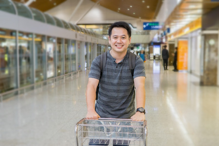 pull along: Young asian Caucasian handsome man pulling luggage hand-cart with bags along airport hall. Passenger in waiting area.travel business concept