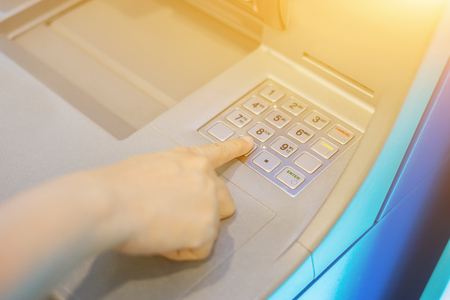 hight tech: woman hand pressing password for withdrawing money from indoor bank ATM,getting thai baht banknotes at Automatic Teller Machine,selective focus,vintage color Stock Photo