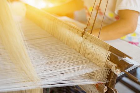 Weben Sie silk Baumwolle auf dem manuellen hölzernen Webstuhl in Laos, Thailand, selektiver Fokus, Weinlesefarbe Standard-Bild - 77164765