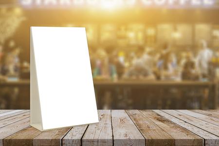 빈 갈색 나무 테이블 및 모의와 커피 숍 인테리어 바 레스토랑에서 메뉴 프레임 종이의 흰 시트와 소책자 스탠드 카페테리아에 아크릴 텐트 카드 배경 스톡 콘텐츠
