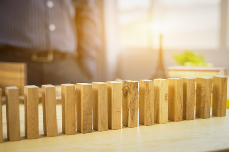 man design to pick one from many wooden blocks.business concept of choosing the right amongst other ones,Planning,risk and strategy,businessman gambling investment,selective focus,vintage color