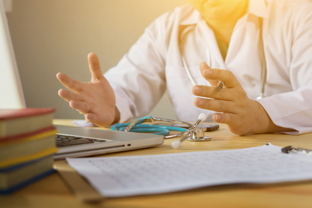 Doctor and patient are discussing something, just hands at the table,explaining prescription to victim,stethoscope and laptop computer on desk in hospital healthcare and medical insurance concept