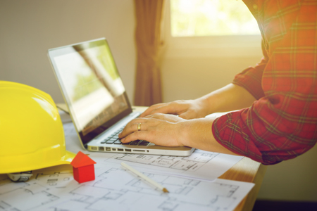 Architect man working with laptop and blueprints,engineer inspection in workplace for architectural plan,sketching a construction project ,selective focus,Business concept Imagens