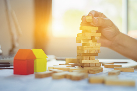 Planning, risk and strategy of project management in business, businessman and engineer  playing a blocks wood game (jenga) on blueprint or architectural project on a tower,construction vintage tone. Imagens