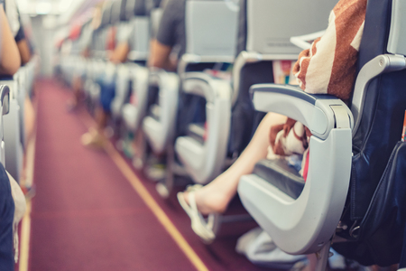 Passenger seat, Interior of airplane with passengers sitting on seats the aisle in background. Travel concept,vintage color,selective focus