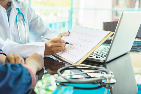 Las manos del doctor que señalan la carta del electrocardiograma en cojín del tablero rellenan historia médica con la pluma. Ayuda del terapeuta cardiólogo, médico hace físico cardíaco, documento de la medida del pulso, idea de la arritmia Foto de archivo - 80626225