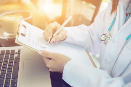Female doctor,surgeon,nurse,pharmacy with stethoscope on hospital holding clipboard,writing a prescription,Medical Exam,Healthcare and medical concept,test results,vintage color,selective focus Stock Photo