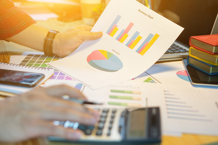 Businessmans hand showing diagram on financial report ,Analysis Brainstorming Business Working in office desk,show the results of their successful teamwork in loft office,vintage color,copy space Imagens