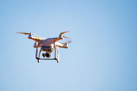 White drone quad copter with high resolution digital camera flying in the blue sky ,selective focus