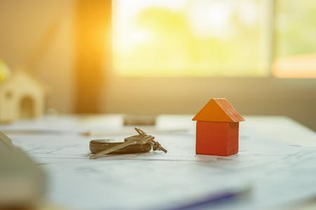 Sluit omhoog symbool van huismodel, hypotheek, investering, onroerende goederen en bezitsconcept, geld en huissleutels, selectieve nadruk, uitstekende kleur