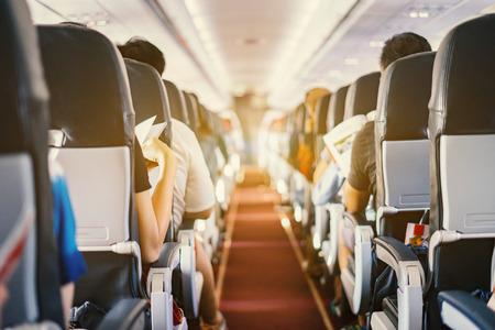조수석, 좌석 및 백그라운드에서 통로 걷고 스튜 어디 스 앉아 승객과 비행기의 내부. 여행 개념, 빈티지 색상, 선택적 포커스 스톡 콘텐츠