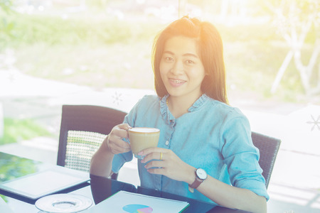 Lächelnd glücklich brunette Frau in guter Laune mit Tasse Kaffee sitzt im Cafe für ralaxing. Heller sonniger Morgen, Vintage Farbe