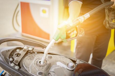 boquilla de combustible de mano en verter a la motocicleta en la gasolinera, enfoque selectivo, color de la vendimia