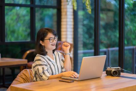 Asiatische Frau arbeitet im Co-Arbeit Raum-Projekt mit generischen Design Laptop. Analyse plant Hände, Mädchen lächelnd und Blick auf digitale Bildschirm, sie überprüft E-Mail, Mailbox über ihre Zahlung Online-Shopping Standard-Bild