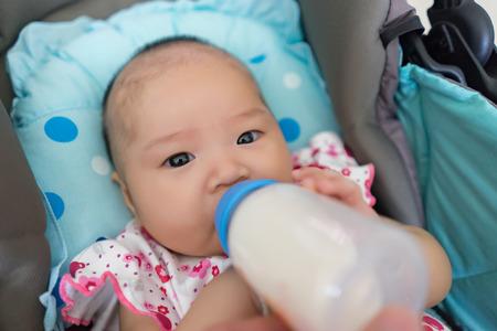 Mutter füttern asiatische Baby mit Milchflasche Großansicht Lizenzfreie Bilder