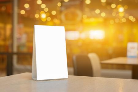 Mock up Label die leere Menü Frame in Bar Restaurant, Stand für Broschüren mit weißen Blättern Papier Acryl Zelt Karte auf Holztisch Cafeteria verschwommen Hintergrund kann den Text des Kunden einfügen. Lizenzfreie Bilder